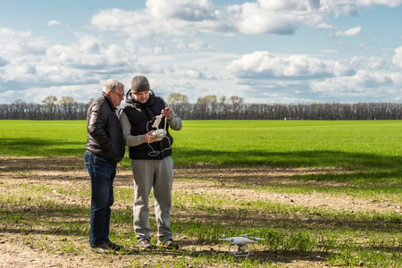 father and son operating of flying drone quadrocopter at the green field