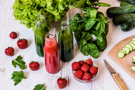 Fresh green smoothies and strawberry smoothie with ingredients on a light wooden background. Healthy detox drinks. Stock Photo