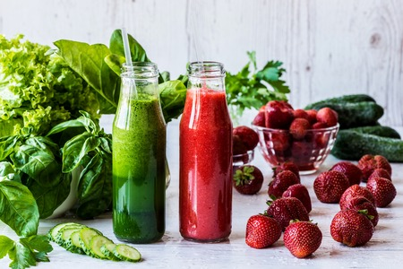Green smoothie and strawberry smoothie in two small bottles with ingredients on a light wooden background. Healthy detox drinks. Stock Photo
