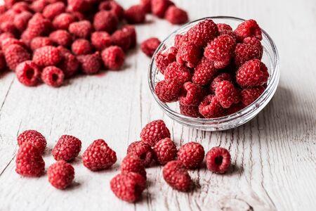 Sweet raspberries in bowl on wooden table