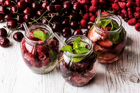 stash: detox water with raspberry, strawberry, cherry on white wooden background. Healthy drinks