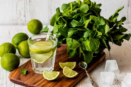 Mojito cocktail with lime, mint and ice on white wooden background.