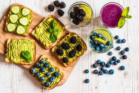 Conjunto de sándwiches de tostadas vegetarianas con aguacate y bebidas. Variedad de alimentos saludables y bebidas sobre fondo blanco de madera Foto de archivo - 82330702