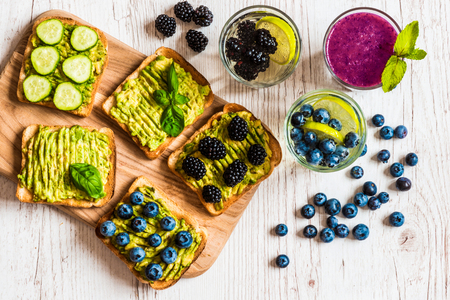 Set van vegetarische toast broodjes met avocado en drankjes. Verscheidenheid van gezonde voeding en drankjes op witte houten achtergrond
