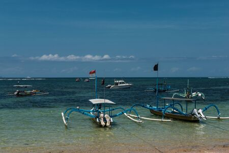 revulsion: Traditional balinese dragonfly boat on the beach. Jukung fishing boats on Sanur beach, Bali, Indonesia, Asia.