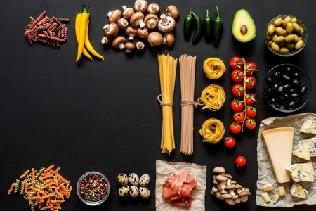 Different fresh ingredients for cooking italian pasta, spaghetti, fettuccine, fusilli and vegetables on a black background with free copy space. Flat lay, top view. Banque d'images
