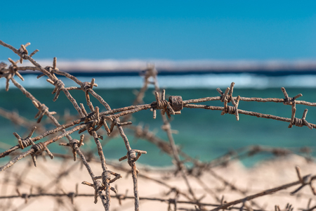 Old barbed wire infront of sea. Wire and blue sky with clouds. Safety fence of barbed wire against the blue sky and sea. Close-up.