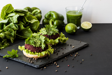 Healthy vegan fastfood burgers with beet cutlet on black background.