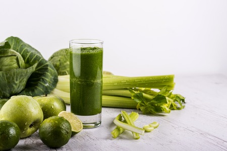 Blended green smoothie with ingredients on wooden table. Dexox drink