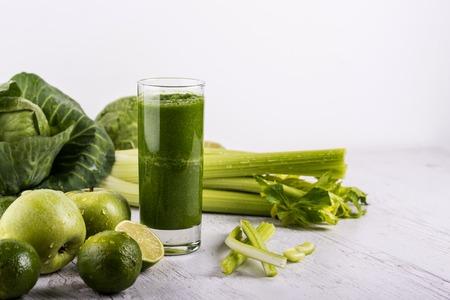 Gemischter grüner Smoothie mit Zutaten auf Holztisch. Dexox-Getränk