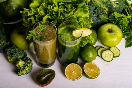 Green smoothie kiwi and cauliflower drinks on white wooden background. Raw food and drink.