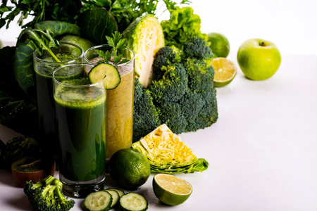 Vegan food and drinks with spinach, kiwi and cucumber on the white wooden background. Raw drinks and foods.