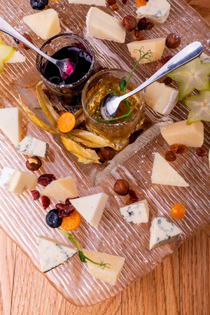 Cheeses with organic cheeses, fruits, nuts and jam on wooden background. Top view. Tasty cheese starter. Imagens