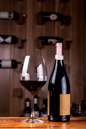 Glass and bottle with delicious red wine on wooden table. In the background Red wine bottles stacked on wooden racks shot with limited depth of field. Imagens