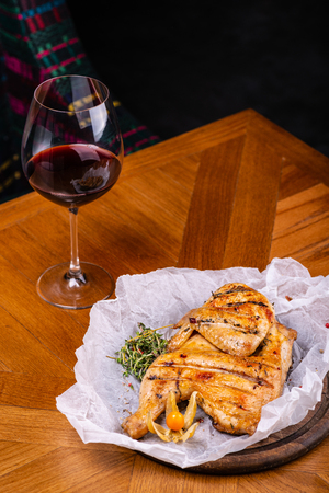 Grilled chicken and glass of red wine of the interior in the restaurant. Imagens