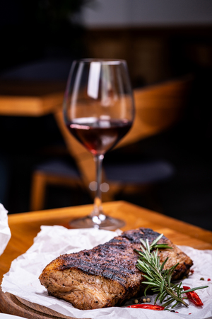 Striploin grilled beef steak served with rosemary, salt and peppercorns on wooden board with glass of wine. Imagens