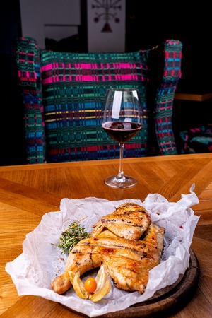 Grilled chicken and glass of red wine of the interior in the restaurant