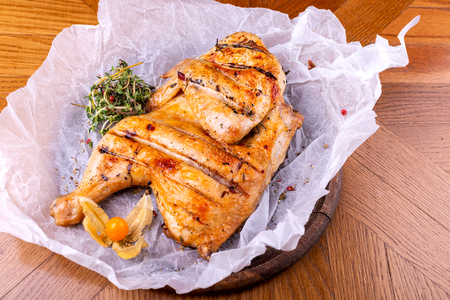 Grilled chicken Tabaka served with herbs on wooden table.