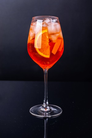 Aperol spritz cocktail in glass on black reflection background.