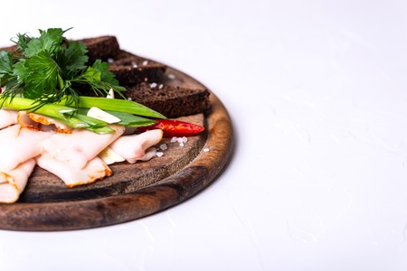 Lard, black bread and greens on a wooden board on a white background. Copy space.