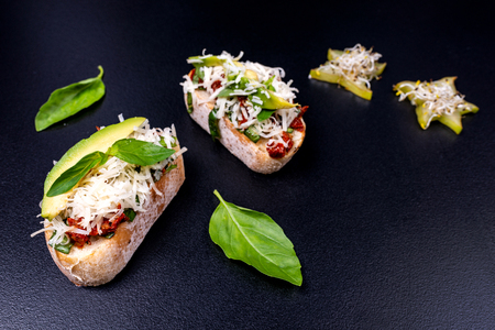 Tasty savory tomato Italian appetizers on black background. Italian food.