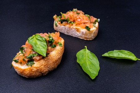 Tasty savory tomato Italian appetizers, or bruschetta, on slices of toasted baguette garnished with basil and avocado