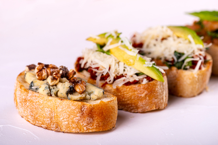 Brushetta set for an aperitif. Variety of small sandwiches with tomatoes, parmesan cheese, avocado and walnut served on a white background