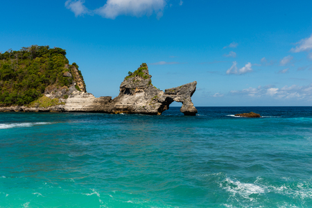 View of tropical beach, sea rocks and turquoise ocean, blue sky. Atuh Beach, Nusa Penida, Indonesia.