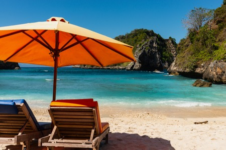 Pair of sun loungers and a beach umbrella on a deserted beach. Perfect vacation concept