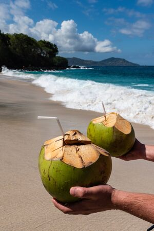 Mens Hands Hold Two Fresh Coconut Cocktails on the Beautiful Beach at Sunny Day. Imagens