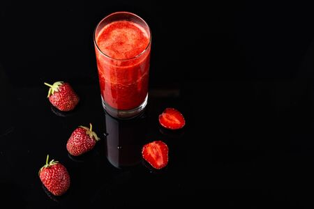 Tasty strawberry smoothie on black background. Fresh strawberry smoothie, summer drink, healthy antioxidant juice with vitamin from ripe fruits Imagens