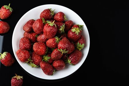Strawberries in a plate on white table top view. Beautiful red strawberry. Imagens