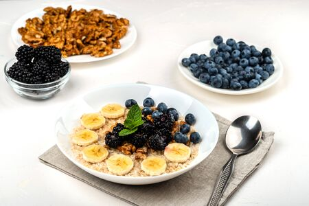 Oatmeal porridge with bananas, walnuts, blackberries, blueberries, honey and mint in a white bowl on a white background. Healthy breakfast and homemade diet food Zdjęcie Seryjne