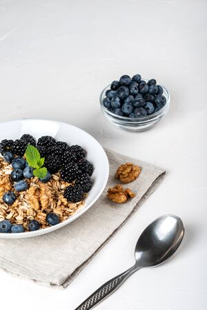 Healthy breakfast. Homemade granola, muesli, cereals with blackberries, blueberries, nuts, honey and mint in a white bowl on a white background Zdjęcie Seryjne