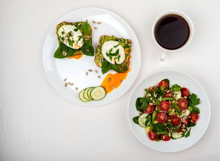 Sandwiches with poached eggs and salad with avocado, cucumbers, cherry tomatoes, spinach leaves, parsley and seeds. Breakfast food on a white background. Top view. Copy space.