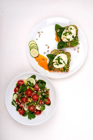 Sandwiches with poached eggs and salad with avocado, cucumbers, cherry tomatoes, spinach leaves, parsley and seeds. Breakfast food on a white background. Top view. 写真素材