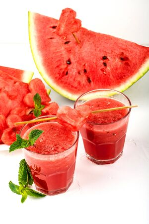 Watermelon smoothie fresh juice with mint, pieces of watermelon in the shape of hearts and slices of watermelon. Healthy drinks in glasses on a white background.