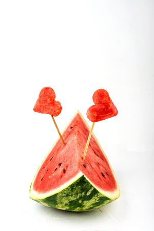 Watermelon with decorated slices in the form of hearts on a white background. Copy space.
