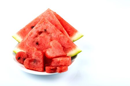 Sliced watermelon in the shape of hearts and ordinary slices on a white background. Copy space. Фото со стока