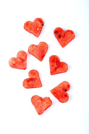 Sliced watermelon in the form of hearts on a white background. Top view. Фото со стока