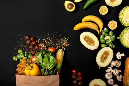 Shopping paper bag full of different fresh vegetables on a black background. Purchases concept. Healthy food organic selection. Top view