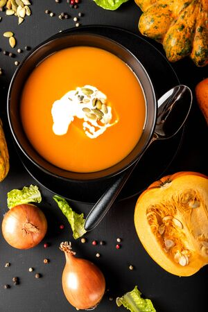 Pumpkin cream soup with milk and pumpkin seeds in a black bowl on the black background. Top view. Autumn healthy vegetarian diet food