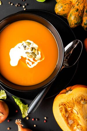 Pumpkin cream soup with milk and pumpkin seeds in a black bowl on the black background. Top view. Autumn healthy vegetarian diet food. Stok Fotoğraf