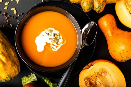 Pumpkin cream soup with milk and pumpkin seeds in a black bowl on the black background. Autumn healthy vegetarian diet food