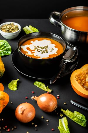 Pumpkin cream soup with milk and pumpkin seeds in a black bowl on the black background. Top view. Autumn healthy vegetarian diet food. Stock Photo