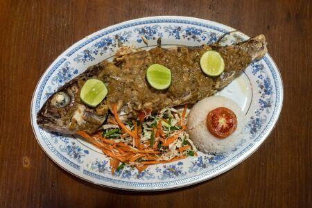 Grilled ocean fish with a side dish and salad on a wooden table.
