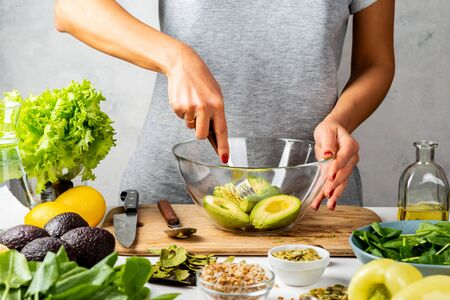 Woman mashing avocado with a fork, cooking guacamole in a glass bowl. healthy food concept