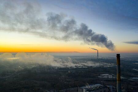 Power plant smokestack at sunrise near the lake. Environmental pollution