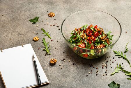 Vegetable salad with arugula, tomatoes, avocado, splashed with balsamic sauce. A book for writing recipes lies on a table. Copy space for text.