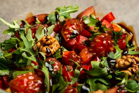 Vegetable salad with arugula, tomatoes, avocado, splashed with balsamic sauce in a glass bowl. Top view. Macro